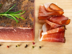 Speck with slices on the cutting board. Typical South Tyrolean smoked bacon. Sliced raw ham. Dry cured meat. Traditional cold cuts, Italian speck with rosemary and pepper.