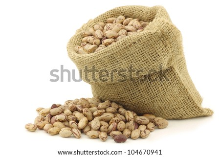speckled beans in a burlap bag on a white background