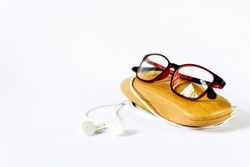 specs, specs box and earphone on white background blurred shallow depth of field