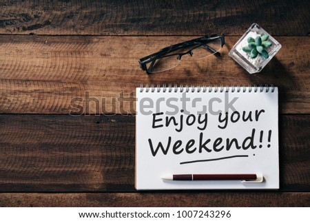 spectacle, cactus and notebook with ENJOY YOUR WEEKEND word on wooden table. lifestyle and relaxation concept