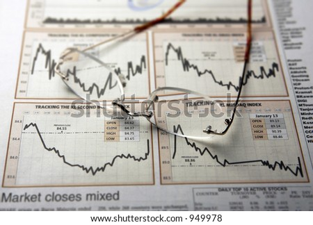 spectacles on newspaper showing financial chart