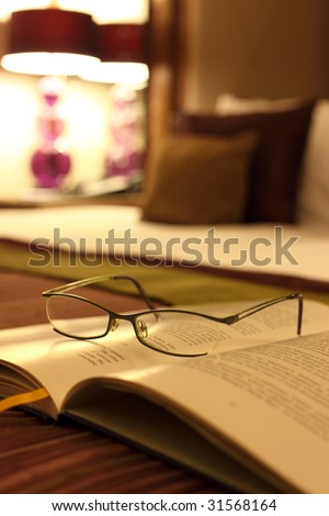 Spectacles resting on an open book on a luxury bed in a hotel room