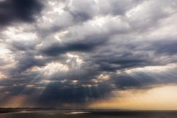 Spectacular and dramatic cloud formations with sun rays shining through gaps in the clouds just after sunrise over the sea at Jeffreys Bay