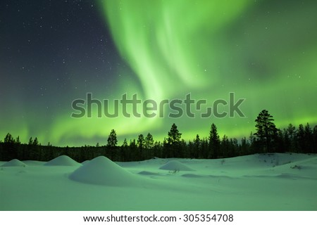 Spectacular aurora borealis (northern lights) over a snowy winter landscape in Finnish Lapland.