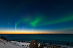 Spectacular dancing green strong northern lights over the famous round boulder beach near Uttakleiv on the Lofoten islands in Norway on clear winter night with snow-clad mountains