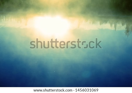 Spectacular dawn (positive mood), time of fog birth. Fog creeps over river on rising sun background. Mist congenerous on sites and then merge into the haze