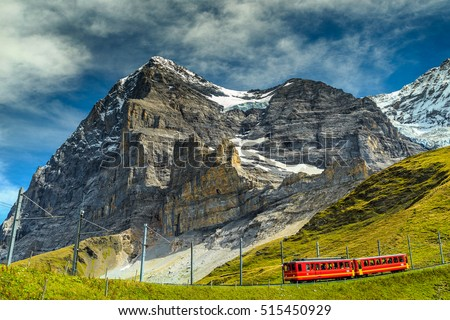 Spectacular famous electric red tourist train coming down from the Jungfraujoch station(top of Europe) in Kleine Scheidegg,Bernese Oberland,Switzerland,Europe