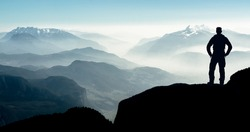 Spectacular layered mountain ranges with valley fog. Man Silhouette reaching summit enjoying freedom.