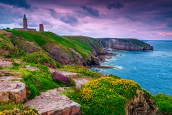 Spectacular lighthouse of Cap Frehel with flowery and rocky coastline at sunrise. Fantastic travel destination in Brittany, France, Europe