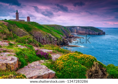 Spectacular lighthouse of Cap Frehel with flowery and rocky coastline at sunrise. Fantastic travel destination in Brittany, France, Europe Foto stock ©