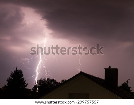 Spectacular lightning strikes a house in an urban area on stormy summer evening