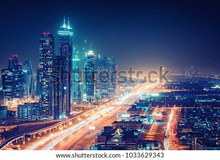 Spectacular nighttime skyline of a big modern city at night\r. Dubai, UAE. Aerial view on highways and skyscrapers.