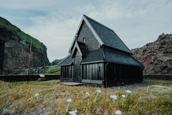 Spectacular Nordic Stave Church in Heimaey, Vestmannaeyjar, Iceland with mountains on the background on a calm summer day.