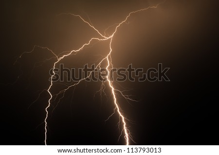Spectacular orange colored lightning strike in the night with no buildings or trees
