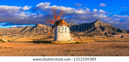 Spectacular scenery of volcanic Fuerteventura. beautiful landscape with windmill over sunset. Canary islands
