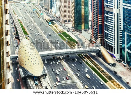 Spectacular skyline of downtown Dubai, UAE.  Famous highway with traffic, metro and skyscrapers. Transportation and travel background.