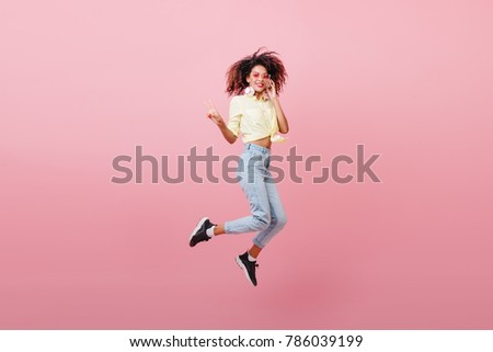 Spectacular sporty woman with brown skin dancing with happy face. Adorable african girl in black sneakers expressing positive emotions.
