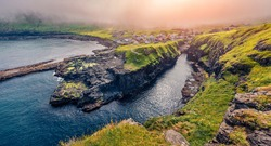 Spectacular sunrise on Gjogv village. Foggy morning scene of Eysturoy island. Colorful Atlantic seascape , Faroe Islands, Denmark, Europe. Traveling concept background.