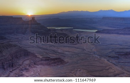 Spectacular sunrise over the purple mesas and and potash ponds seen from Dead Horse Point Overlook in Dead Horse Point State Park, UT