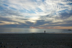 spectacular sunset with beach goer in silhouette