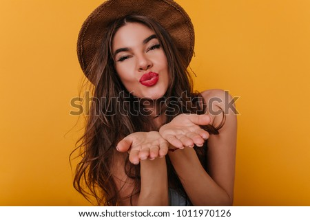Spectacular tanned girl with bright makeup sending air kisses after photoshoot. Indoor photo of blissful young woman with bronze skin expressing positive emotions.