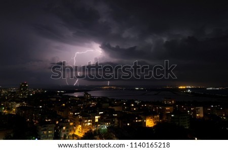 Spectacular Thunderstorm in dark night sky above city