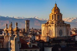 Spectacular view from the roofs of the historic center of the city of Turin, with the dome of the church dedicated to S. Lorenzo and the mountains of the Western Alps in the background.