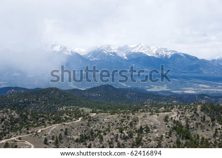 Spectacular view of a mountain range in the Rockies near Salida, Colorado, with a tiny road and foothills in the foreground.