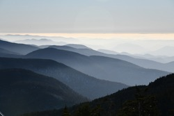 Spectacular view of mountain ranges silhouettes and fog in valleys during sunset time at Stowe, Vermont, USA