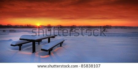 Spectacular winter sunset with a table and benches covered with snow - stock photo