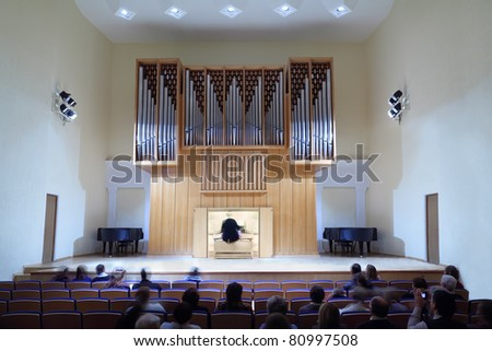 spectators are sitting on seats and watch performance - woman playing on large organ