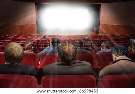 spectators in hall of cinema with movie collage