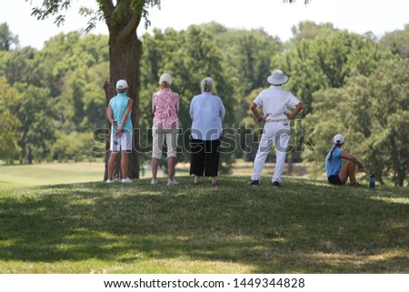 spectators stand around the 18th and final hole to watch a golf tournament #1449344828