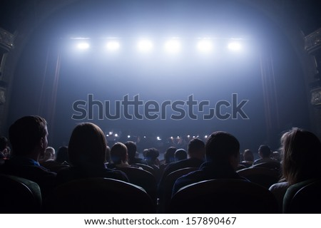 Spectators wait for the start of the concert sitting in the chairs in the auditorium.