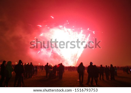 Spectators watch a fireworks display at a Guy Fawkes event, also known as Bonfire Night which happens annually in the United Kingdom on November 5.  Image has copy space.