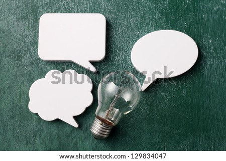 speech bubbles and the light bulb on the blackboard - stock photo