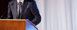 Speech of an abstract man in a suit on stage at the stand for performances. Tribune or pulpit for speaker official, president or professor. Close-up. Copy space.
