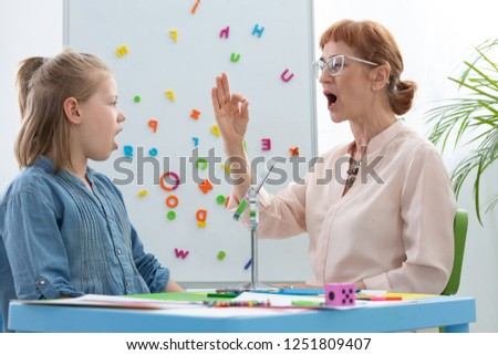Speech therapist teaching vowels to a girl