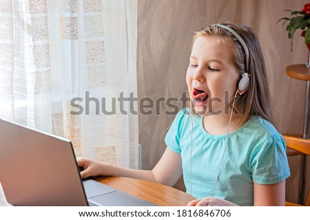 Speech training concept. Little girl uses a laptop to study at home with a teacher, a speech therapist. Distance learning. A kid doing exercises for correct pronunciation.