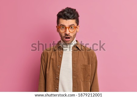 Speechless unshaven man looks in stupor drops jaw from astonishment cannot believe in shocking relevation wears optical glasses and brown shirt poses against pink background. Human emotions concept Foto d'archivio ©