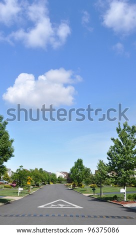 Speed Bump Children Crossing Caution Sign on street of suburban neighborhood on beautiful blue sky day