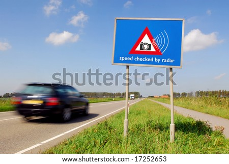 Speed checked by radar roadsign in rural landscape and speeding car with motion blur