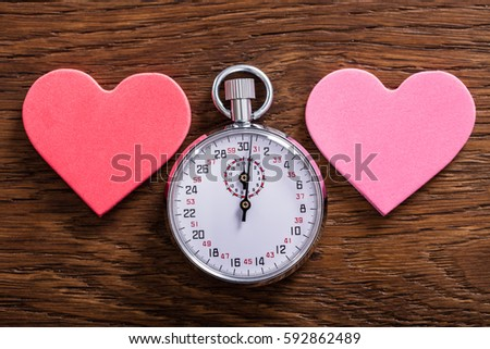 Speed Dating Concept. Two Heart Shapes And A Stop Watch On Wooden Desk #592862489