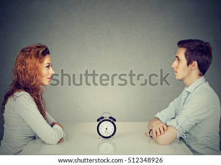 Speed dating. Man and woman sitting across from each other at table with alarm clock in-between   #512348926