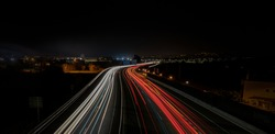 Speed lights on the road with long exposure. List of cities and towns at the background: Barcelona, Platja d'Aro, Calonge, Sant Antoni de Calonge, Palamós.