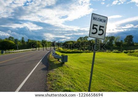 speed limit sign in the green of the Canadian countryside with a storm on the horizon #1226658694