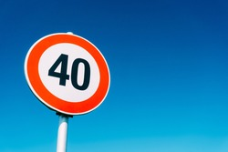 Speed limit sign 40 kilometers per hour, against the blue sky.