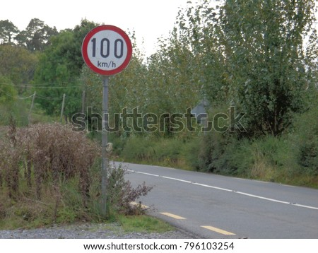 Speed limit sign showing 100 km/hr speed limit along rustic road #796103254