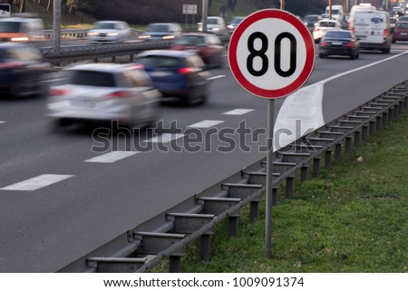 Speed limit sign with a traffic in the background #1009091374