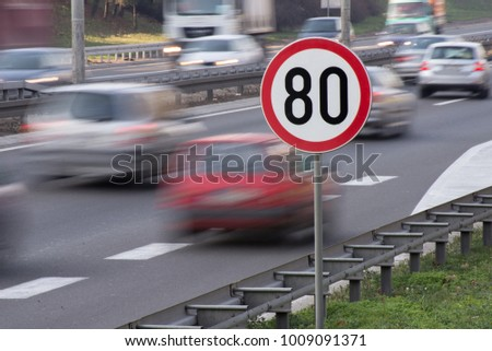 Speed limit sign with car passing in motion blur #1009091371